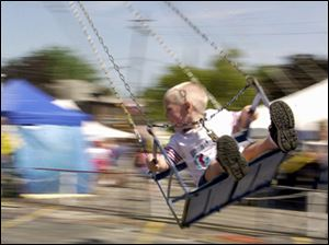 Vincent Dupuis, 3, of Toledo, holds on and laughs as he spins around on the swing ride at the Birmingham Ethnic Festival, in this 2002 file photo.