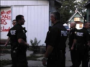 Members of the gun task force search the back of an abandoned home on Hollywood Ave., where gangs are known to hang out.