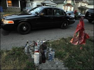 An unmarked police car, with an arrested suspect in the back seat, sits in front of a memorial of liquor bottles and a red bandanna that still remain on Hollywood Avenue for Victor Johnson, who was gunned down on Sept. 17, 2009.