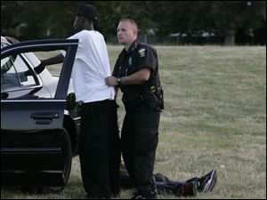 Toledo police Sgt. William Shaner pats down a man hanging out at the Inez Nash Park for drugs and weapons.