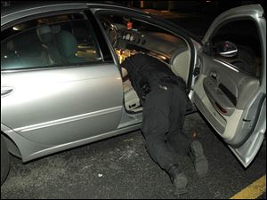 Toledo Police Department's Paul Marchyok searches a car for weapons and drugs.