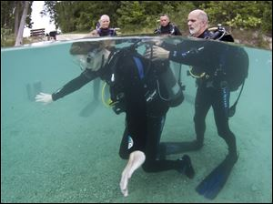Instructor Jeff Davis, left, holds onto John Harris as he dips under the water. Ashley Harris and Jason Thor look on.