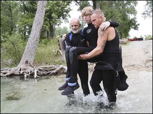 Scuba instructor Jeff Davis, left, and dive control specialist Jason Thor carry John Harris down to the water.