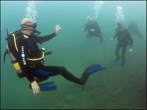 Dive instructor Jeff Davis signals to Ashley Harris, left, an John Harris, right, asking if they are OK.