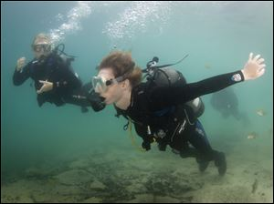 John Harris, right, swims using his hands as he and sister Ashley Harris, left, scuba dive in White Star Park.