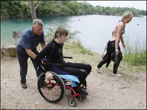 Rod Harris pushes his son John back toward the vehicle after he and sister Ashley, right, finished their dive.