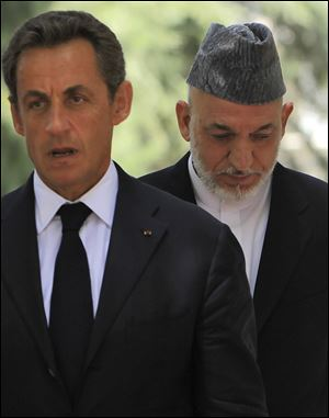 Afghan President Hamid Karzai right, walks along with French President Nicolas Sarkozy to address a news conference Tuesday at the presidental palace in Kabul, Afghanistan. Karzai says his half brother's assassination reflects the suffering of all Afghan people.
