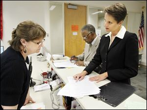 Michelle Wagner, right, and Judge C. Allen McConnell, center, who is seeking a third term, file petitions to run for openings on the Toledo Municipal Court bench. Lori Jacek of the elections board is at left.