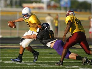 Gold Squad quarterback Matt Spragg (12) is sacked by Black Squad defender Jake Phillips (12).