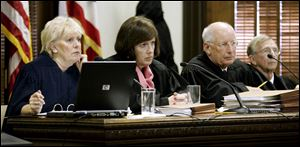 Ohio Supreme Court Justices Judith Lanzinger, left, and Paul Pfeifer, right, could not run again unless the mandatory retirement age is raised or lifted. Between them during a 2009 hearing was Justice Maureen O'Connor, now the court's chief justice.
