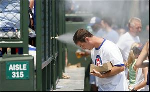 Ross Perry uses the mist-maker at Wrigley Park to cool off from the 95-degree heat before his favorite team, the Cubs, squares off  against the Marlins in Chicago.