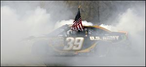 Ryan Newman does a burnout while holding the American flag Sunday after winning at New Hampshire Speedway.