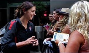 Alex Morgan greets fans after she and other members of the U.S. soccer team arrived in New York's Times Square on Monday.