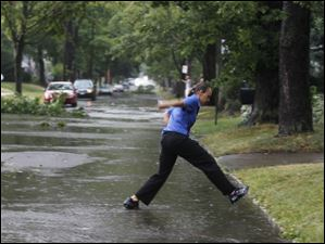 Laquell Burmeister jumps over flood water near her curb on her way home from work.