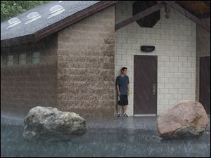 Michael Goldsmith, of Sylvania, finds shelter from the rain at a restroom in Fossil Park while taking a three mile run.