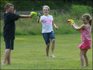 Brooklyn Tolson, 6, right, and her sister Kaitlyn Tolson, 10, center, have a squirt gun battle with their cousin Alex Walker, 9, at Side Cut Metro park in Maumee.