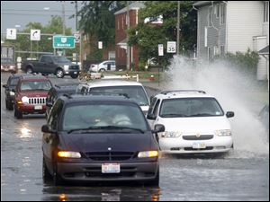 Traffic makes its way around a van stuck in flood water on Central Avenue past Monroe Street after a downpour.