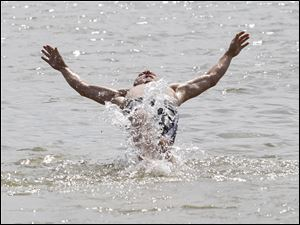 Aaron Imber, of Toledo, falls back into the water on a scorching day at Maumee Bay State Park.