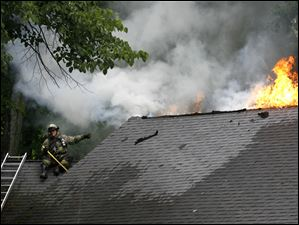 A fireman sits of the roof of 1240 Beverly Hills Dr. in Toledo as he battles a fire caused by a lightning strike during a thunderstorm. No one was hurt.