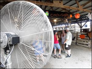 A huge fan blows on fair goers in the
