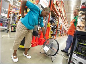 Assistant manager Doug Schlachter plugs in a fan so Emma Collins, Toledo, can feel the output at Home Depot on Airport Highway. Ms. Collins said her air conditioner has gone out.