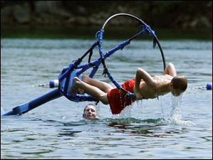 Sylvania resident Kevin Schweickert, 13, dips into the water from the basket of a bobber at the Centennial Quarry.