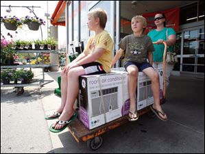Kaylene Palmer of Adrian pushes out a cart containing two air conditioners as her sons, Austin, 9, left, and Ian, 7, hitch a ride at Home Depot on Airport Highway.