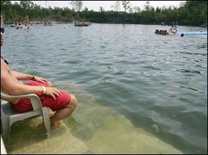 Toledoan Tyler Wilkie, 20, submerges a chair and his ankles into the water to keep cool while life guarding at the Centennial Quarry in Sylvania.