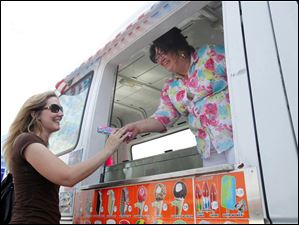 Julie Wood, from Holland, gets a free bubblegum ice cream from Mr. Frosty's Kim Diehl during the free 'Key to Safe Teen Driving' class at Owens Community College.