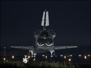 Space Shuttle Atlantis comes to a complete stop at the Kennedy Space Center landing strip.