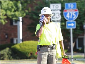 Mel Smith-Agin, a Shelly Company employee out of Findlay, wipes the sweat off of her face while directing traffic and construction vehicles at the corner of Briarfield Blvd and Salisbury Road where there is ongoing construction.