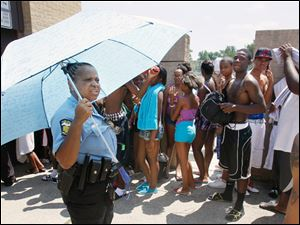Officer Burna Guy informs people that Willys Park Pool is at capacity and that no one else will be let in.