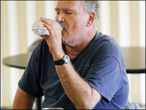 Robert Samberg drinks water at the Eleanor M. Kahle Senior Center. He went to the cooling center to beat the heat.