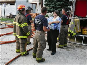 Sue Dykstra, Forester, Mich, delivers water to firefighters battling a fire on Buffalo Street Thursday night. Dykstra and her boyfriend Dan Gohlke, Toledo, delivered two cases of water to the firefighters to help them cool off.