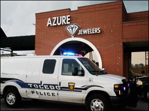 A Toledo police van sits in front of Azure Jewelers in the Executive Shoppers Center after a robbery Friday afternoon.