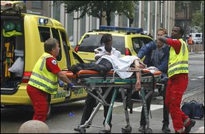 A victim is carried to a waiting ambulance in central Oslo.