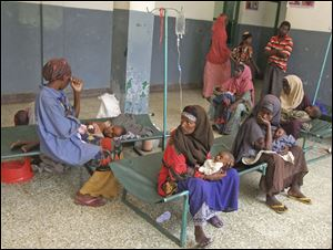 Somali women sit with their children as they are treated in Banadir Hospital in Mogadishu, Somalia. Drought and lack of food force migrations for aid and medical help.