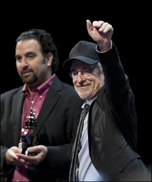 "Steven Spielberg, right, stands on stage with Comic-Con programming director Eddie Ibrahim during the panel for ""The Adventures of Tintin."""