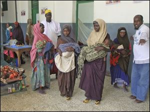 Women from southern Somalia and their malnourished children line up for services at Banadir hospital.