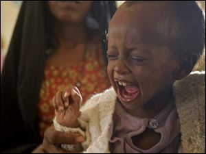A child cries from hunger in the border town of  Dadaab, Kenya.