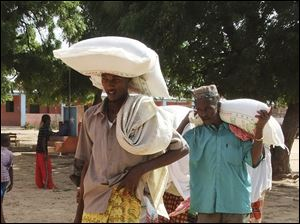 Men from southern Somalia carry food rations received at a displaced camp in Mogadishu, Somalia.