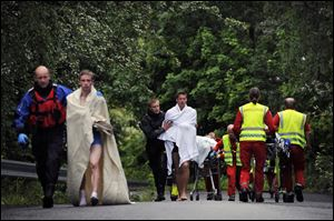 Medics and emergency workers escort youths from a camp site on the island of Utoya, Norway, Saturday.