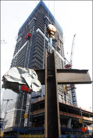 The September 11 cross stands in front of 4 World Trade Center during a ceremony, Saturday, July 23, 2011, in New York. After the ceremony, the cross was installed at the National September 11 Memorial and Museum. It was discovered upright in the ruins of ground zero following the attacks of Sept. 11, 2001.