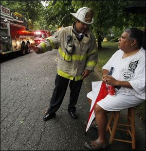 Ex-Toledo City Council president Louis Escobar speaks with Toledo Fire Chief Luis Santiago after evacuating his South Toledo home.