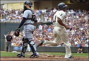 Minnesota Twins' Ben Revere, right, scores behind Detroit Tigers catcher Alex Avila, left, on a single by the Michael Cuddyer during the first inning Saturday.