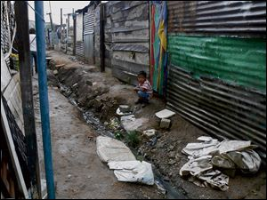 A young boy crouches by an open sewer in a dump workers' ghetto.