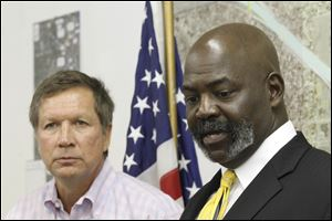 Gov. John Kasich, left, listens as Toledo Mayor Michael Bell speaks during the news conference.