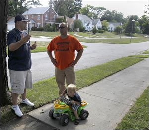 Oregon resident Scott Schultz, left, tells his neighbor Tom Lambrecht about the attempted abduction of his son, Tyler, 2, on tractor, in front of their Eastmoreland Drive home.