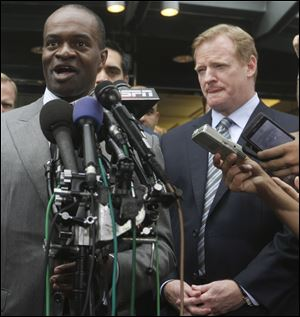 DeMaurice Smith of the players' union speaks after the lockout ended as Commissioner Roger Goodell listens.