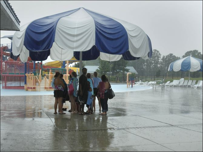 Rolf Park Pool Swimmers huddle under an umbrella at Rolf Park Pool in Maumee as they wait for the thunderstorm to pass through the area.